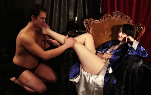 Aeryn Walker in a purple robe, reclining on a throne with a man at her feet, in the porn film The Fantasy Project by Louise Lush for Bright Desire
