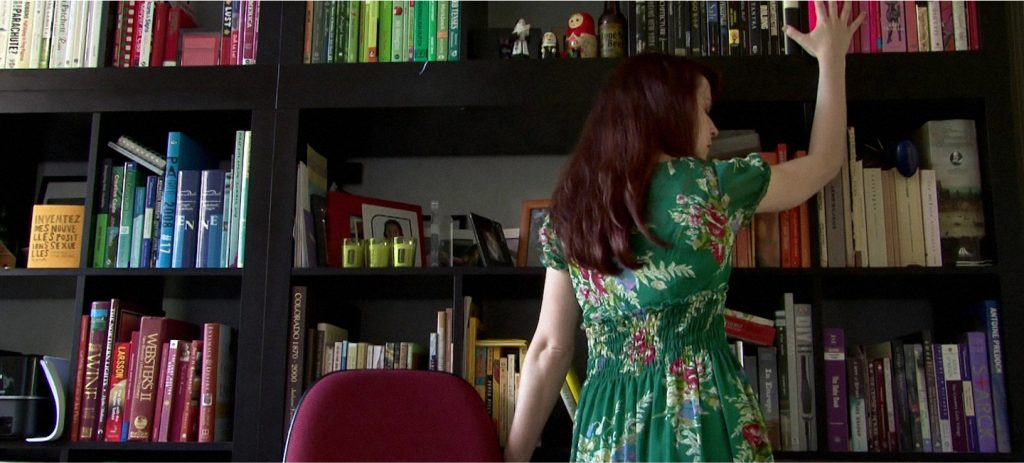 AnnaBelle Lee caresses a bookshelf in Silver Shoes (The Housesitter), an erotic trilogy directed by Jennifer Lyon Bell for Blue Artichoke Films