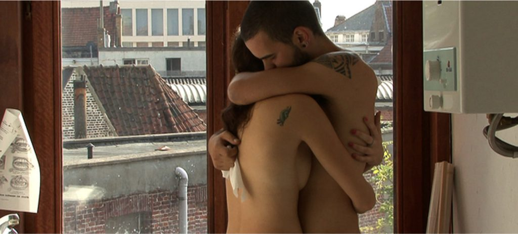 Wim Van Damme and Floor Wyns hug in the bathroom in in Skin.Like.Sun. (Des Jours), an erotic documentary movie directed by Jennifer Lyon Bell and Murielle Scherre available at Blue Artichoke Films